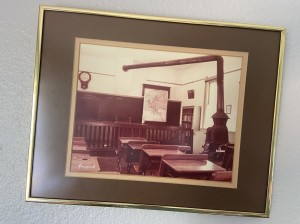 A photograph of an old schoolhouse classroom, hanging crooked on the wall