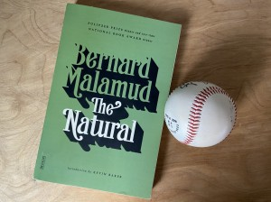 "A copy of Bernard Malamud's ""The Natural"" next to a baseball"